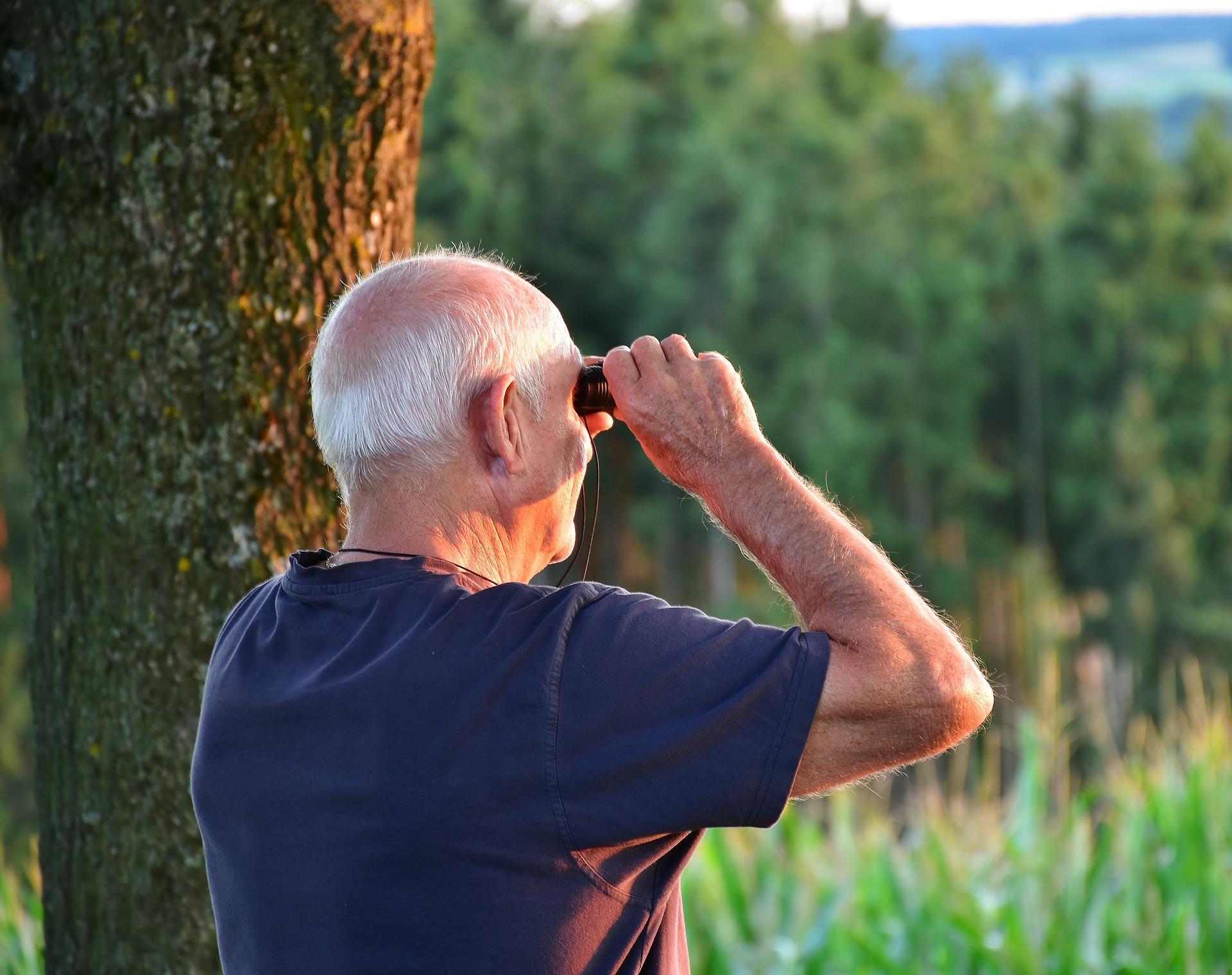 Senior schaut mit Fernglas in die Ferne. Foto: RitaE/pixabay.com